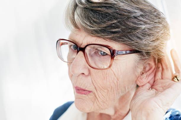 Vieille dame souffrant de baisse de l'audition qui porte la main à son oreille pour mieux entendre