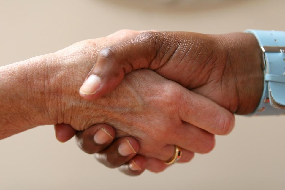 Poignée de main entre une aide-soignante et sa patiente