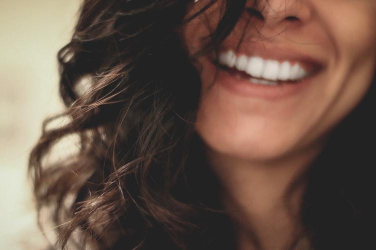Jeune femme au beau sourire grâce à sa couronne dentaire