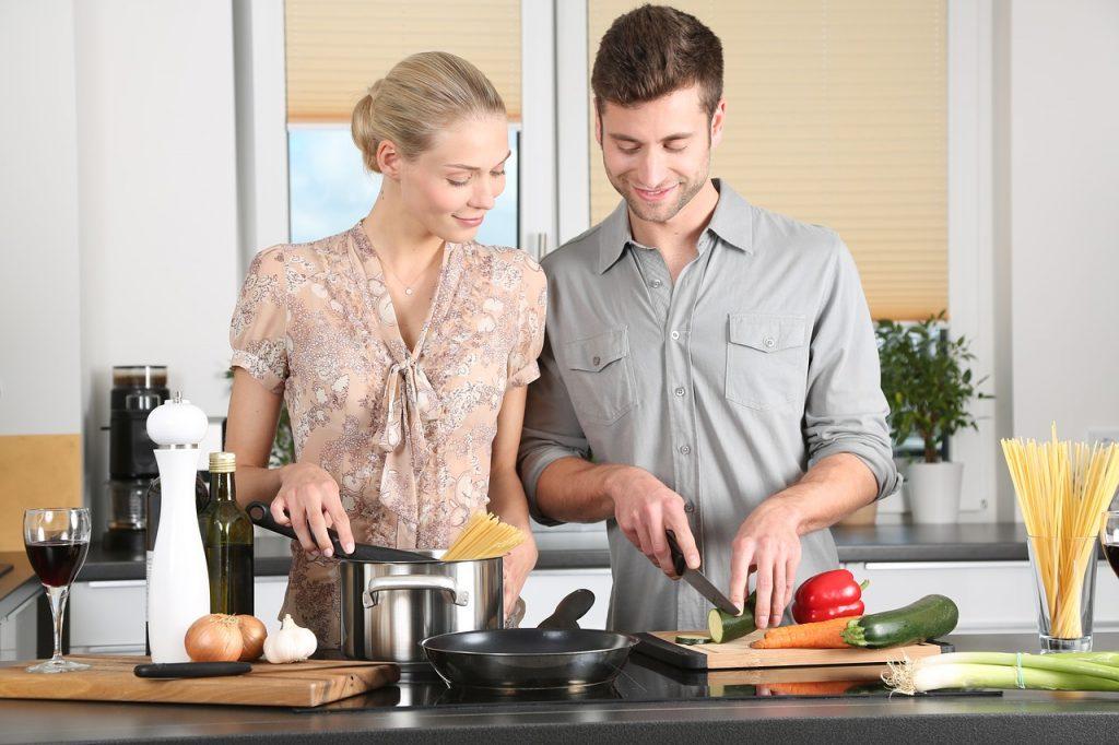 un homme et une femme qui cuisinent ensemble l'homme coupe des légumes et la femme fait cuire des pâtes