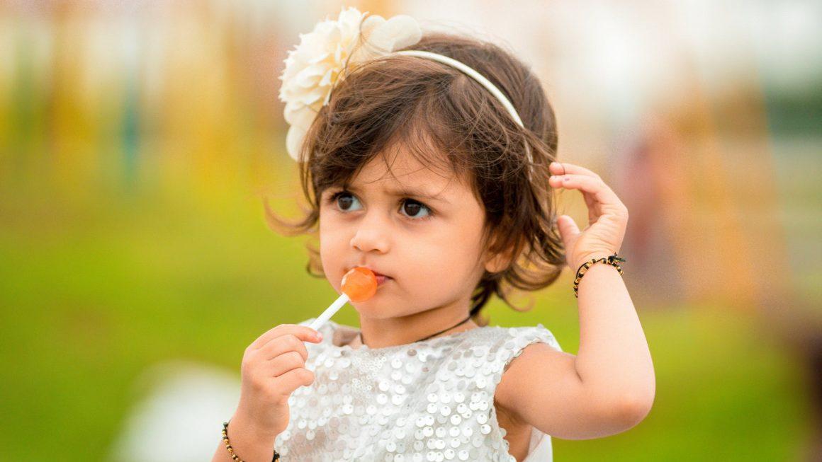 Petite fille qui mange une sucette au risque de devenir obèse
